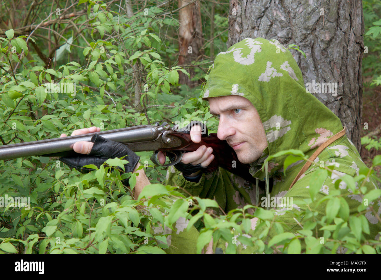 The shooter in camouflage with an old trigger gun Stock Photo