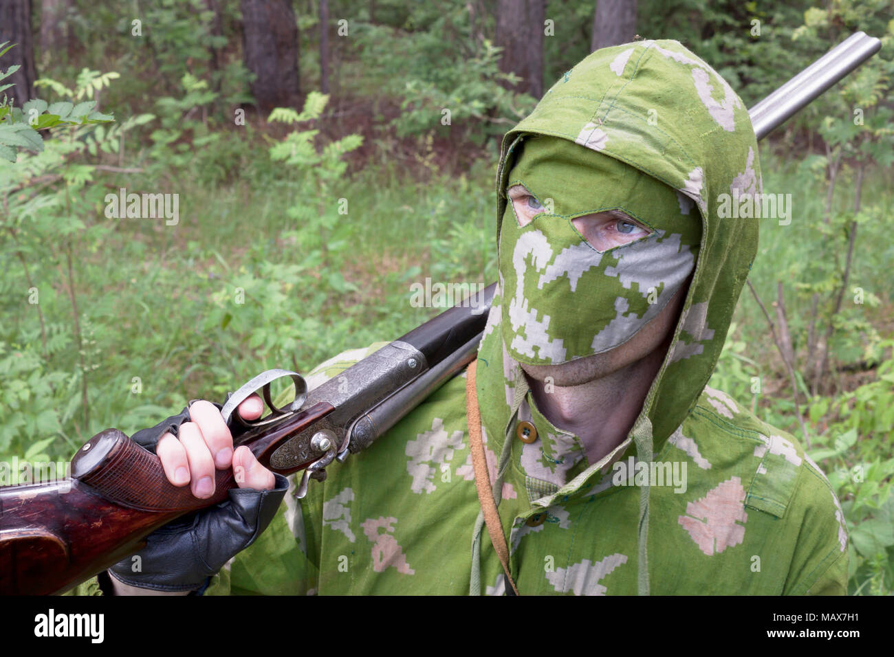 The shooter in camouflage with an old gun Stock Photo