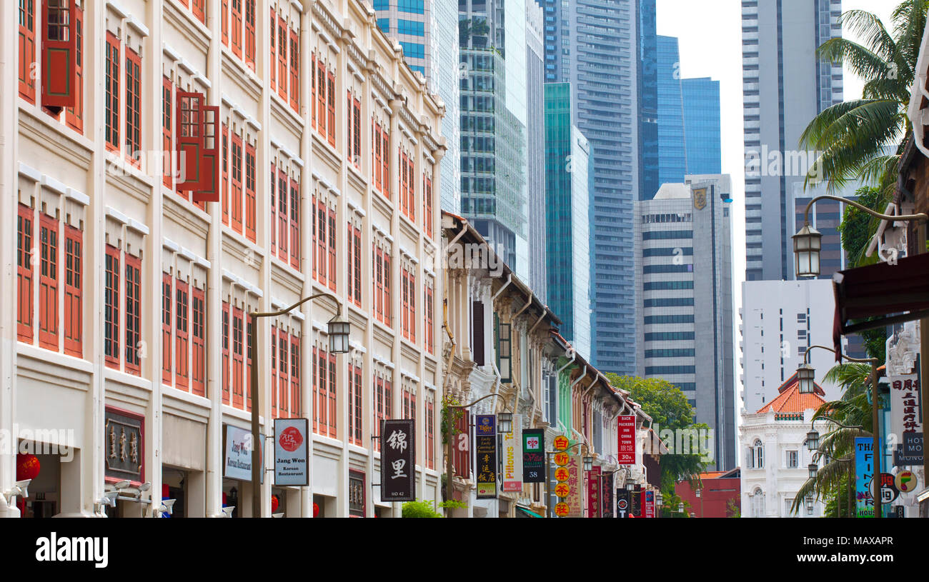 old houses with coloured shutters with the cities financial sky scrapers in the distance in Singapore - Stock Image