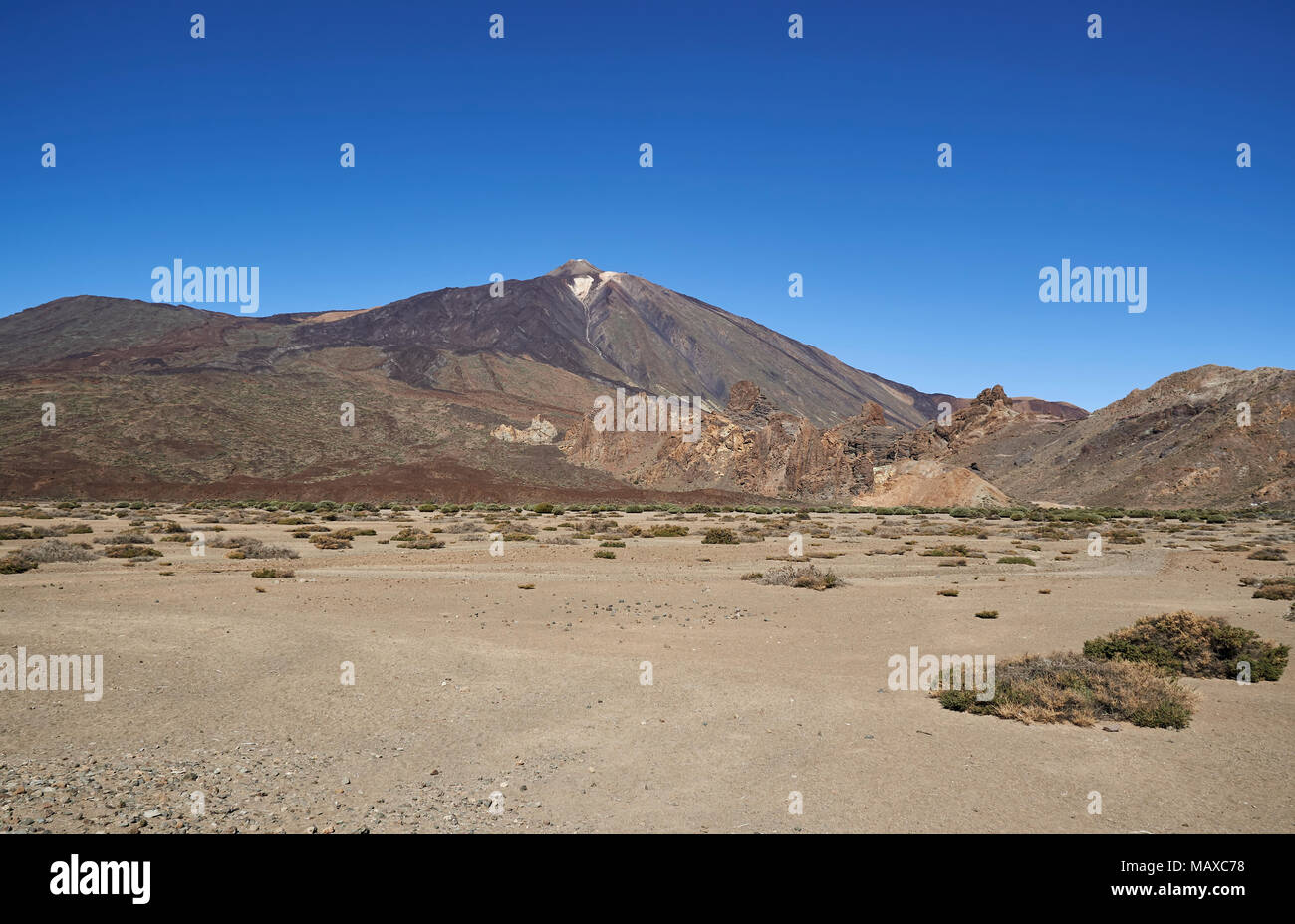 Mount Teide in Tenerife, rising up from the surrounding Desert floor, filled with sand and debris from previous Lava flows and eruptions. - Stock Image