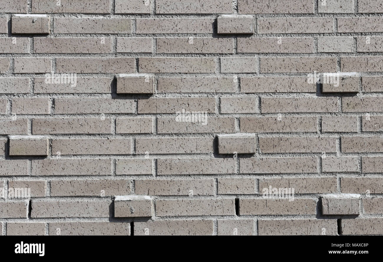Grey brick wall with horizontal lines and beautiful symmetry. Nice piece of architecture to be used as a background or texture photo. - Stock Image