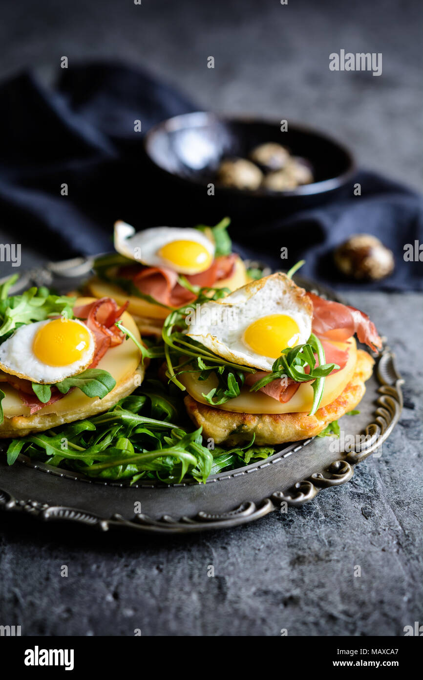 Savoury yoghurt and scallion pancakes with Black Forrest ham, smoked cheese slices, quail egg and arugula - Stock Image