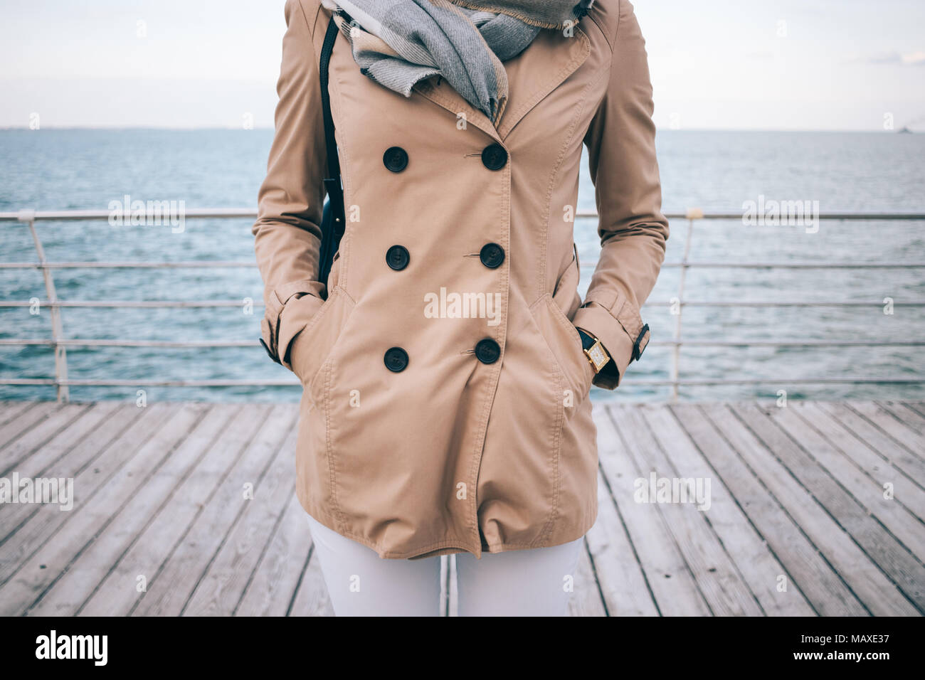Spring marine outfit. Fashionable girl standing on the waterfront. Cropped photo of slender young woman wearing beige trench coat, large scarf and gol - Stock Image