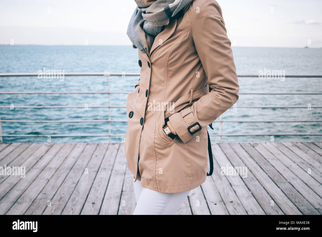 Fashionable girl standing on the waterfront. Cropped photo of slender young woman wearing beige trench coat, big scarf and gold wrist watches. Details - Stock Image
