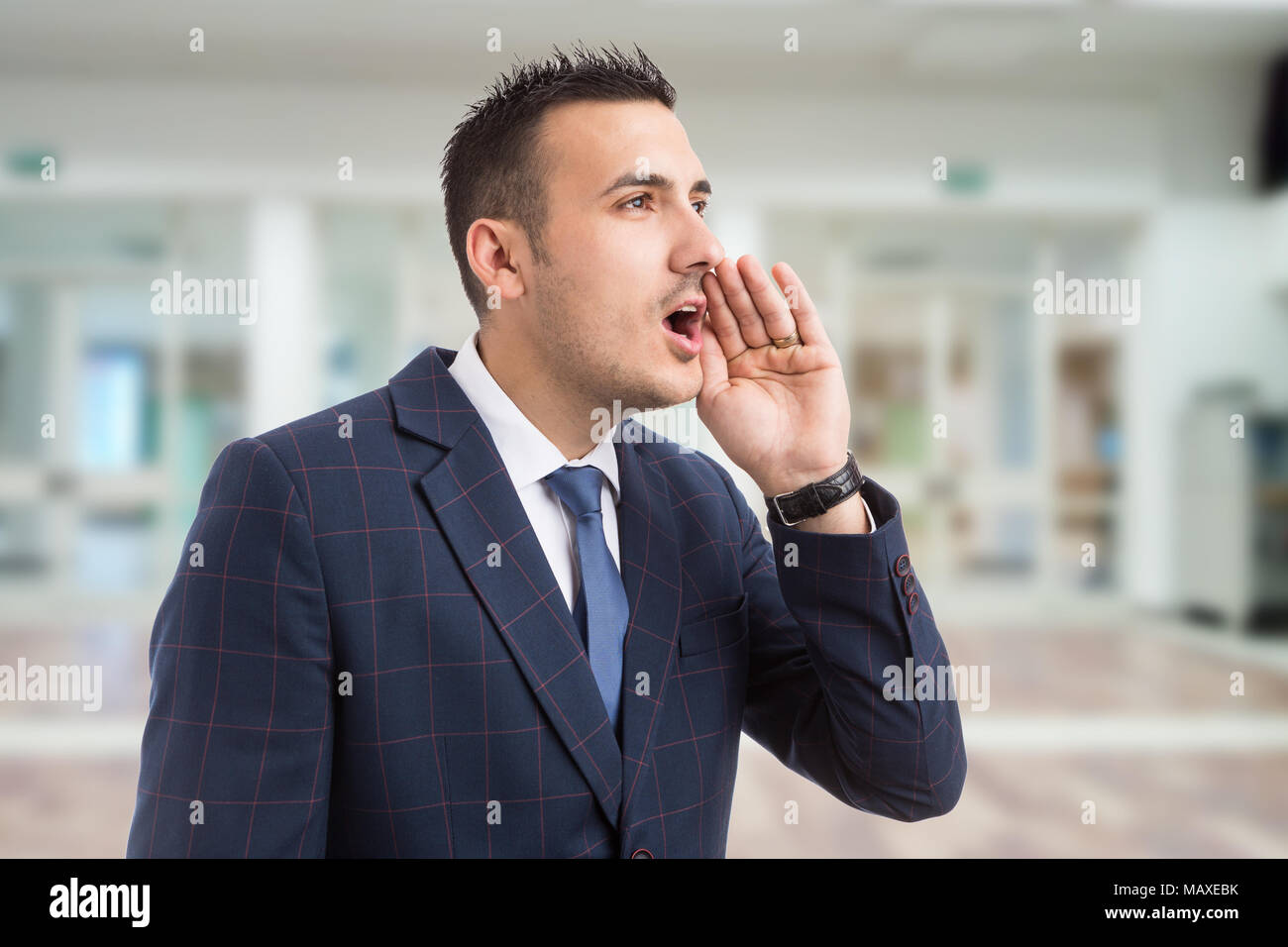 Young real estate agent or realtor shouting with hand on mouth as loudly calling or yelling on lobby background - Stock Image