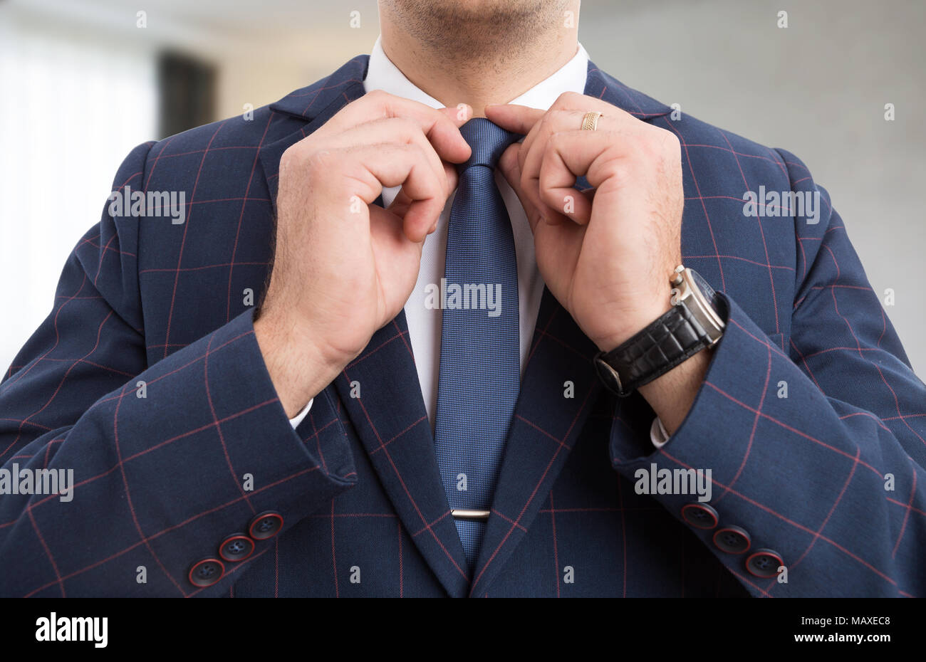 bb97b6a8ec08 Male businessman hands adjusting blue tie as luxury expensive men clothing  - Stock Image