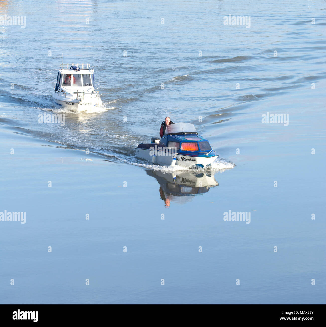 Two small motor boats moving slowly on still waters - Stock Image