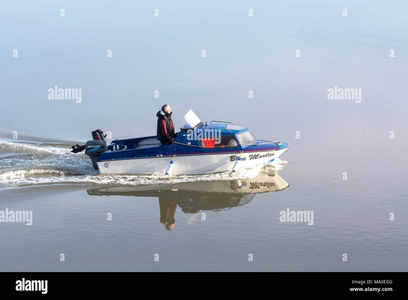 Small motor boat moving slowly on calm water - Stock Image
