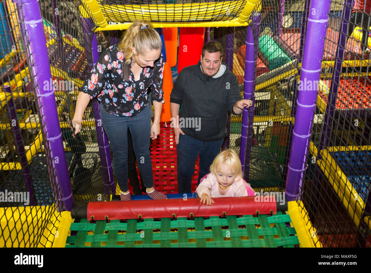 parents with child climbing stair at Cosmic Adventures indoor playground, Ottawa, Ontario, Canada - Stock Image