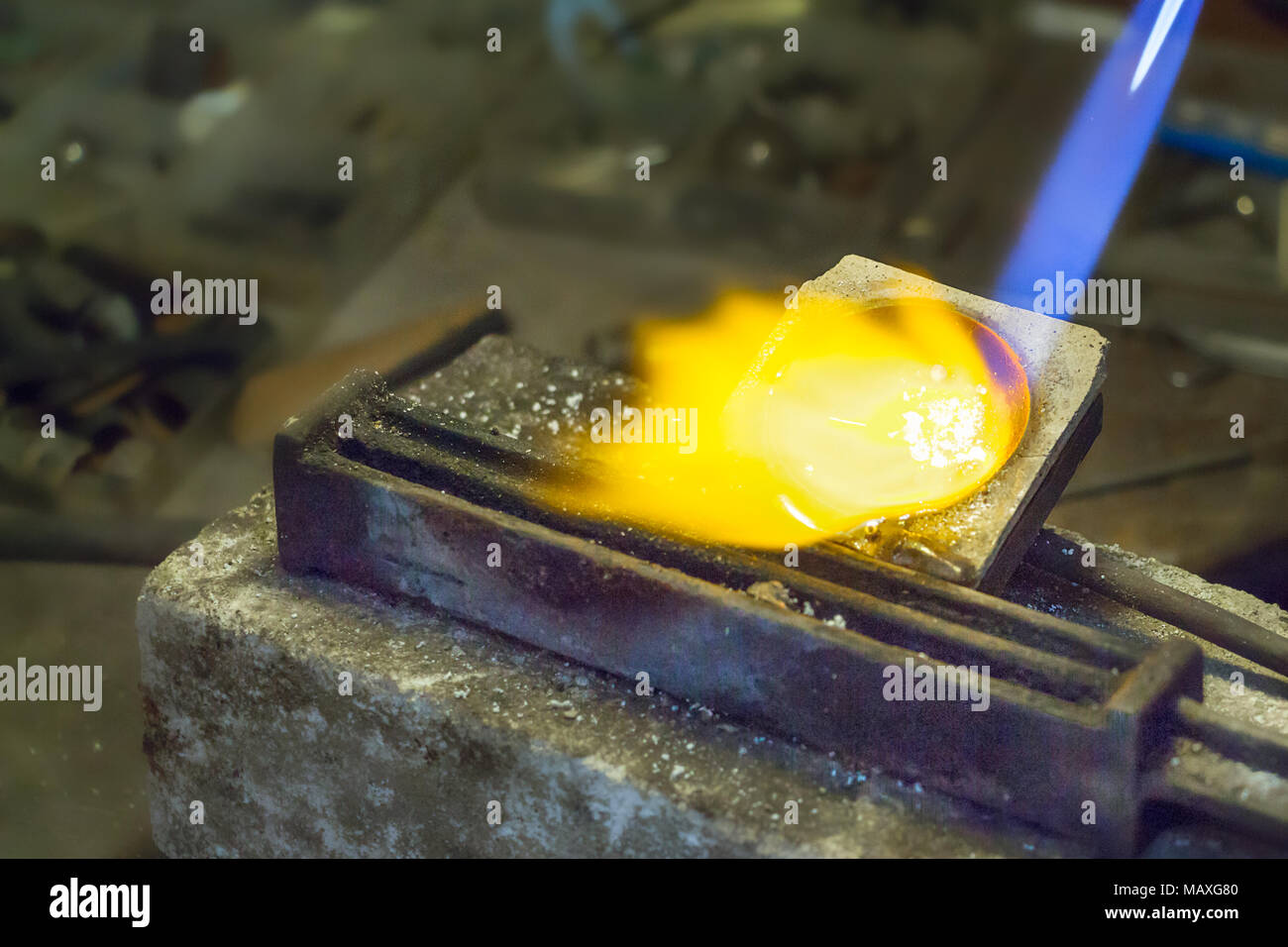 Jeweler putting melting silver on wire ingot mold using a gas - oxygen torch. - Stock Image