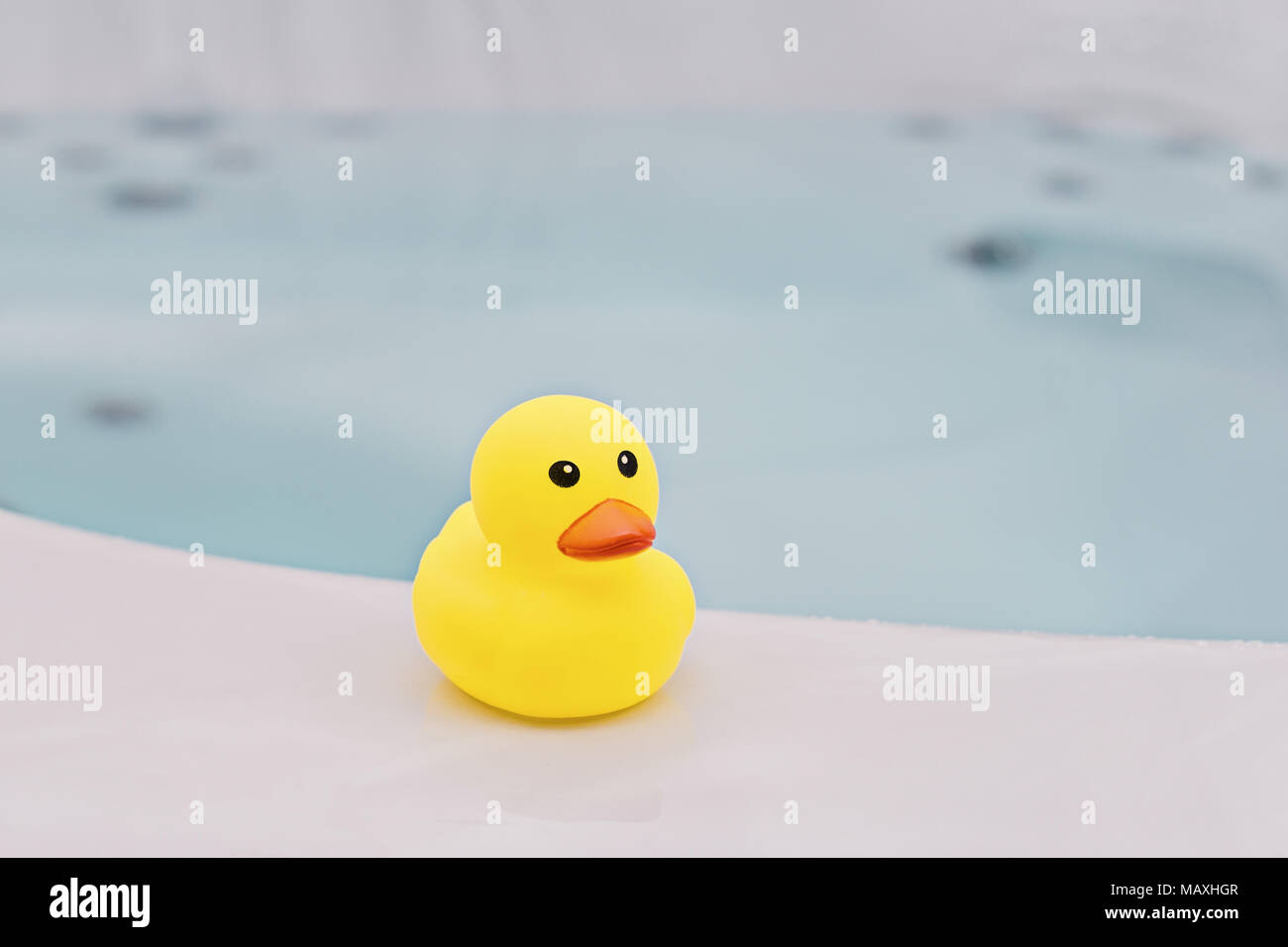 Small yellow rubber duck in bathroom background. Bath time concept ...
