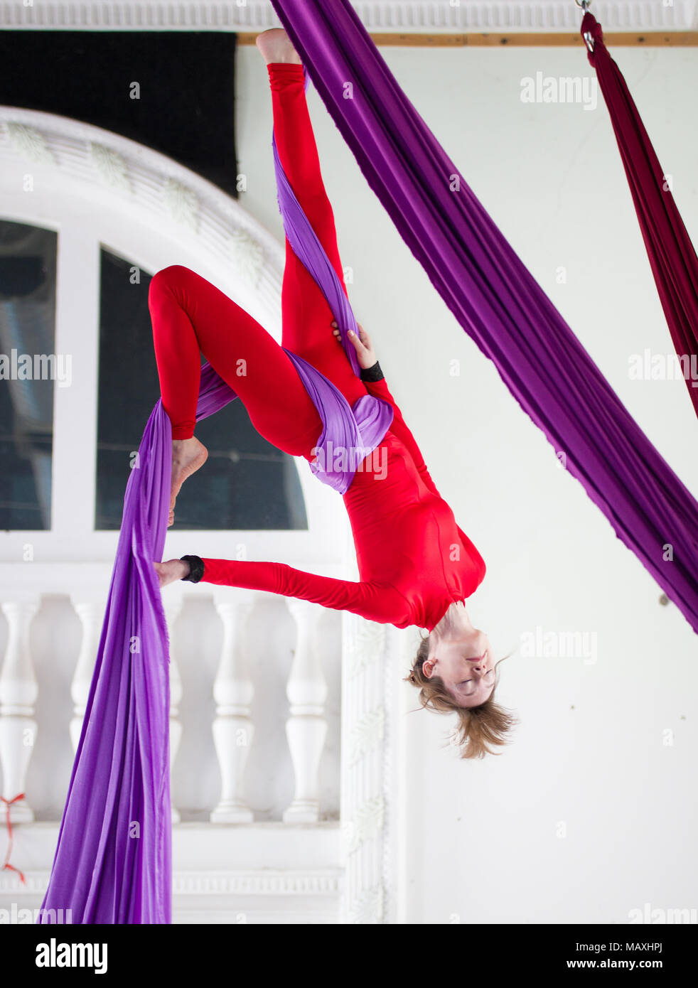 Young attractive air gymnast performs an exercise hanging on aerial silk - Stock Image