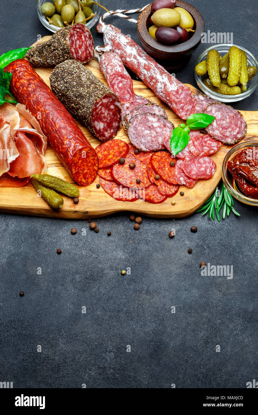 Set of traditional Italian meat snack. Salami, prosciutto, olives, capers - Stock Image