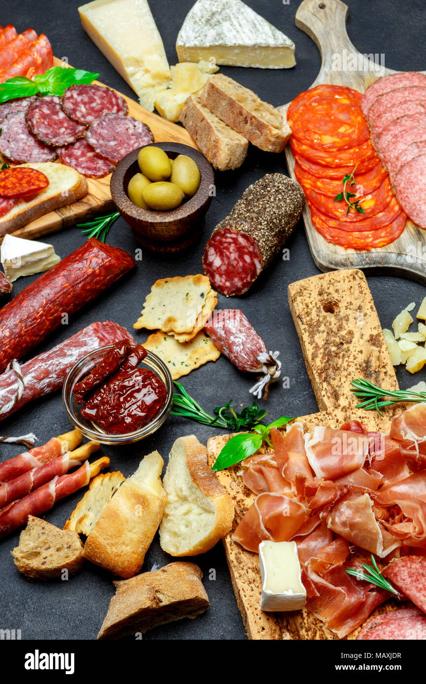 Italian meat appetizer snack set. Salami, prosciutto, bread, olives, capers - Stock Image