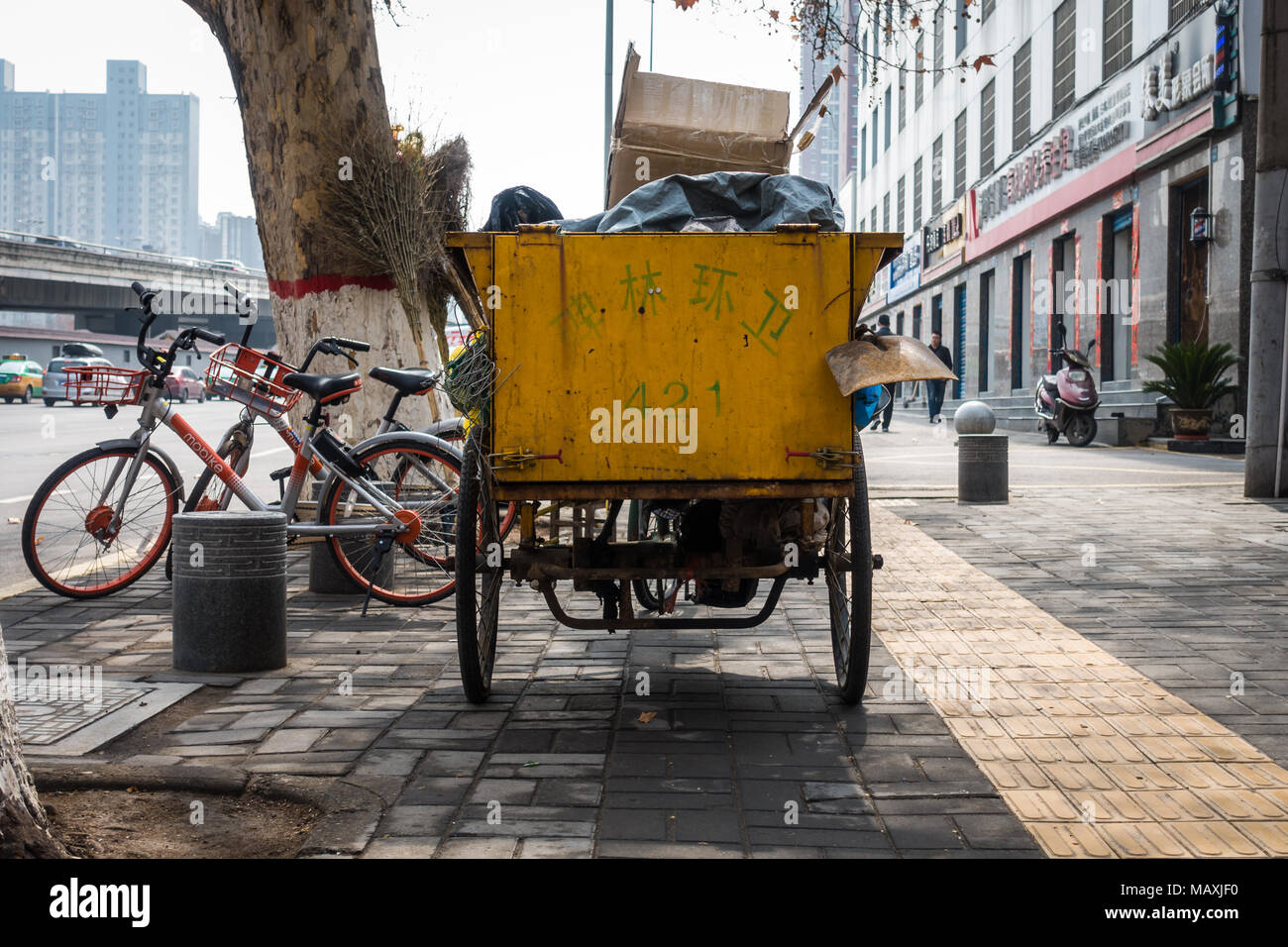 Chinese Trash Collection Wagon Parked on the Sidewalk During Workday in Xian, March 2018 - Stock Image
