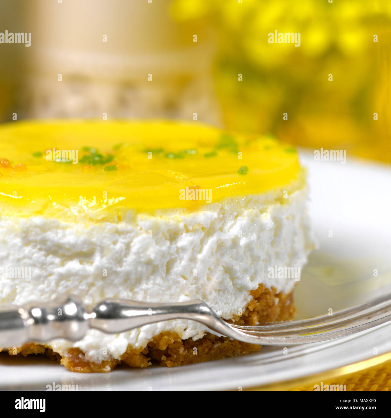 restaurant setting of a lemon mousse cheesecake a silver fork on a white plate soft background with  yellow flowers and to ad copy space - Stock Image
