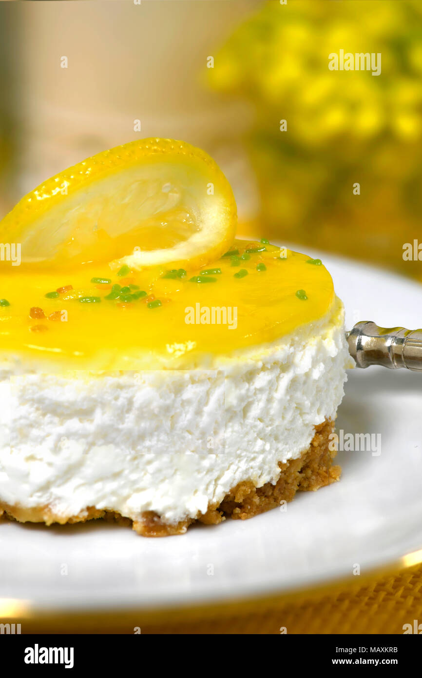luxury restaurant setting of a lemon mousse cheesecake a silver fork on a white plate soft background with  yellow flowers and to ad copy space - Stock Image