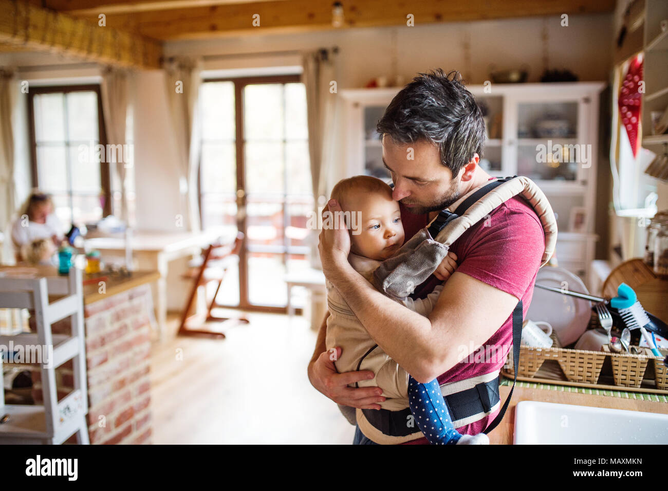 Father with a baby girl in a carrier at home. - Stock Image