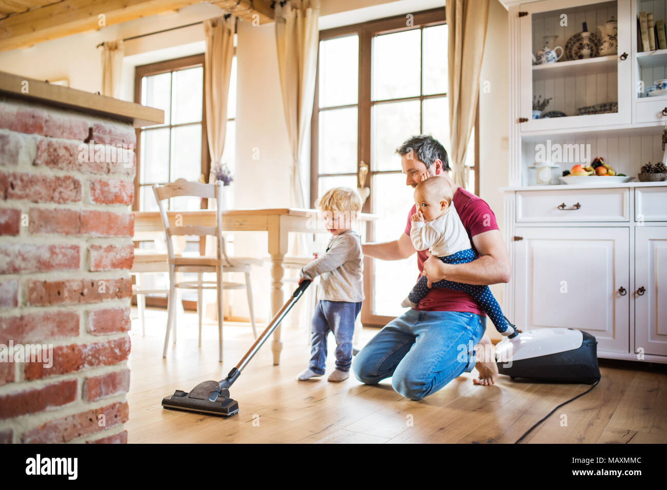 Father and two toddlers doing housework. - Stock Image