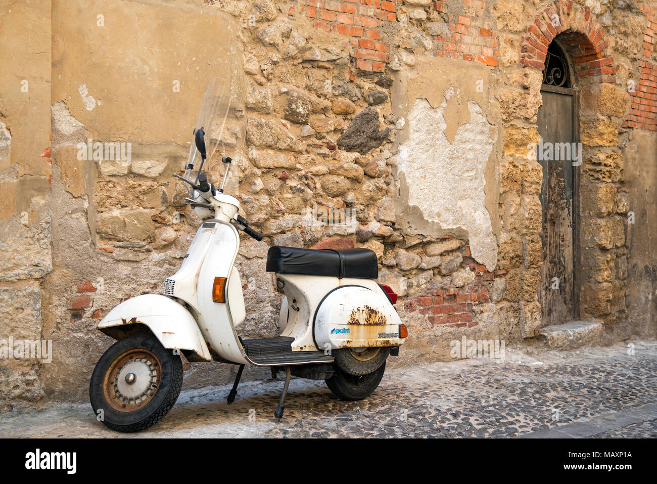 An old rusted white Vespa PX125E scooter parked by the walls of Chiesa della Badiola church in Cefalu, Sicily. - Stock Image
