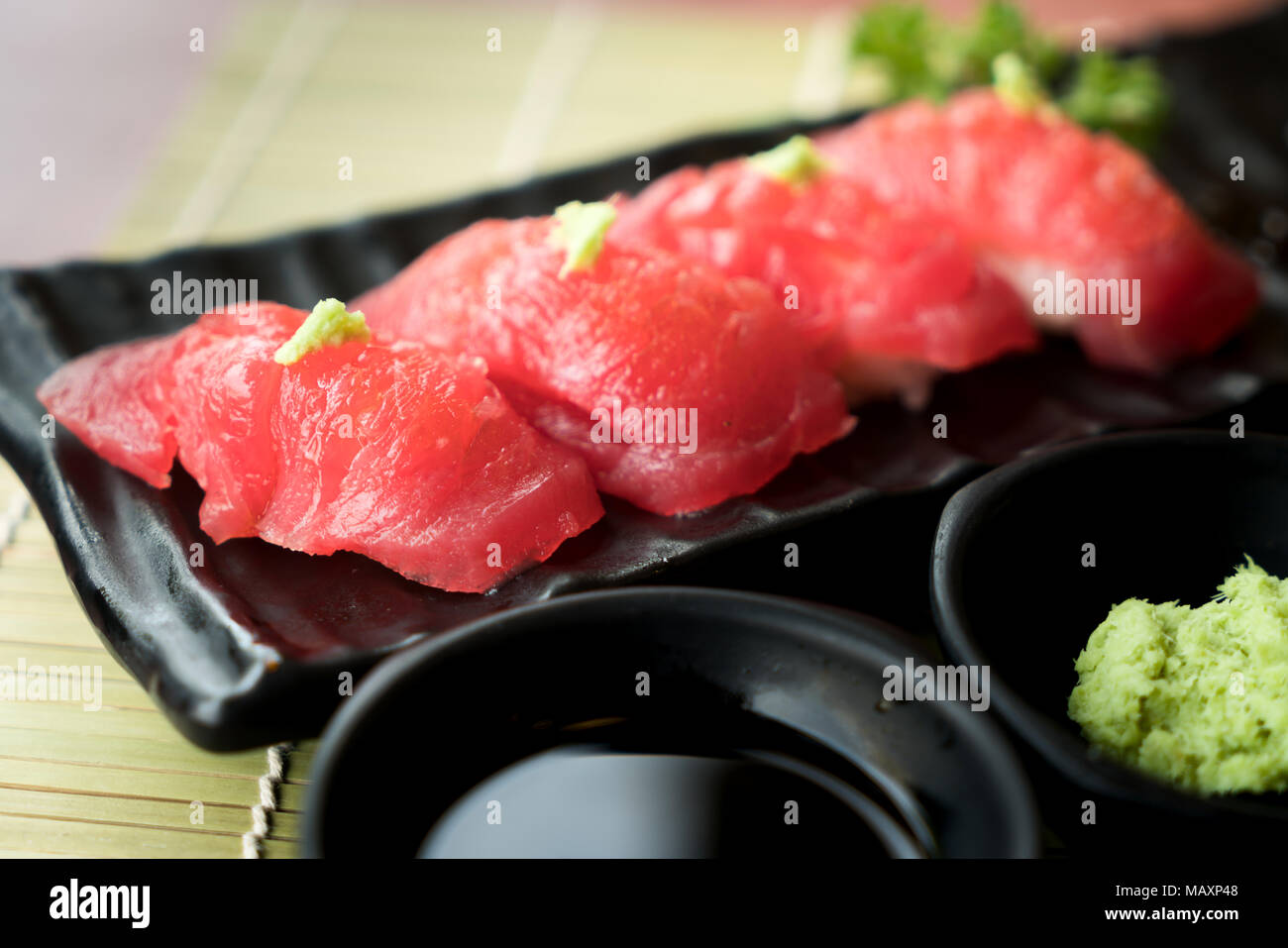 Tuna Sushi On Black Plate Along With Anese Sauce And Green Leaf Decoration Food Close Up At