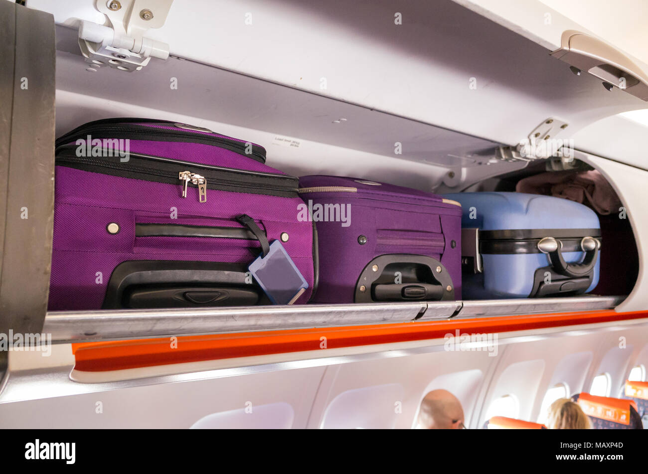 Carry-on cabin bags in the overhead luggage lockers on an easy jet plane, UK - Stock Image