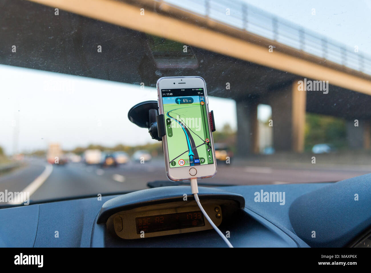 Using TomTom satnav app on iPhone while driving on motorway, UK - Stock Image