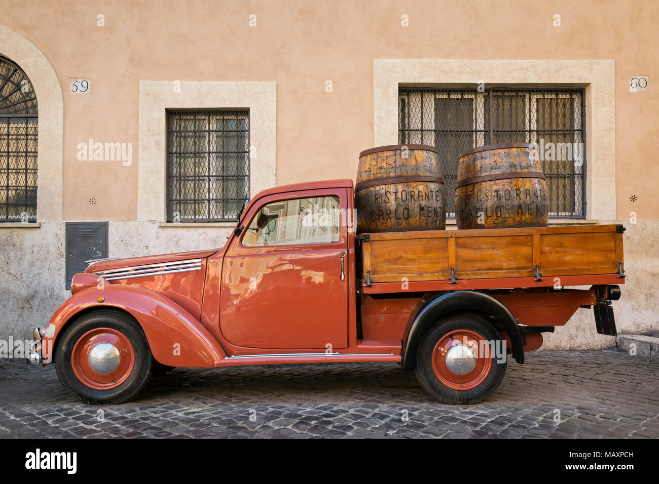An old red Fiat 1100 flat bed van with wooden wine barrels in the back, parked outside Ristorante Carlo Menta in Rome, Italy. - Stock Image