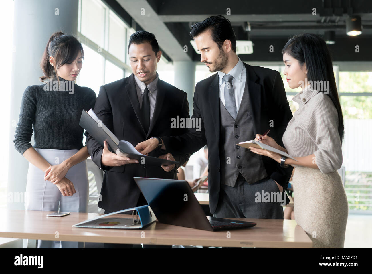 Smart manager explaining internal meeting to his project team in modern office. The multi ethnic business person group in suit. Project and Business c - Stock Image