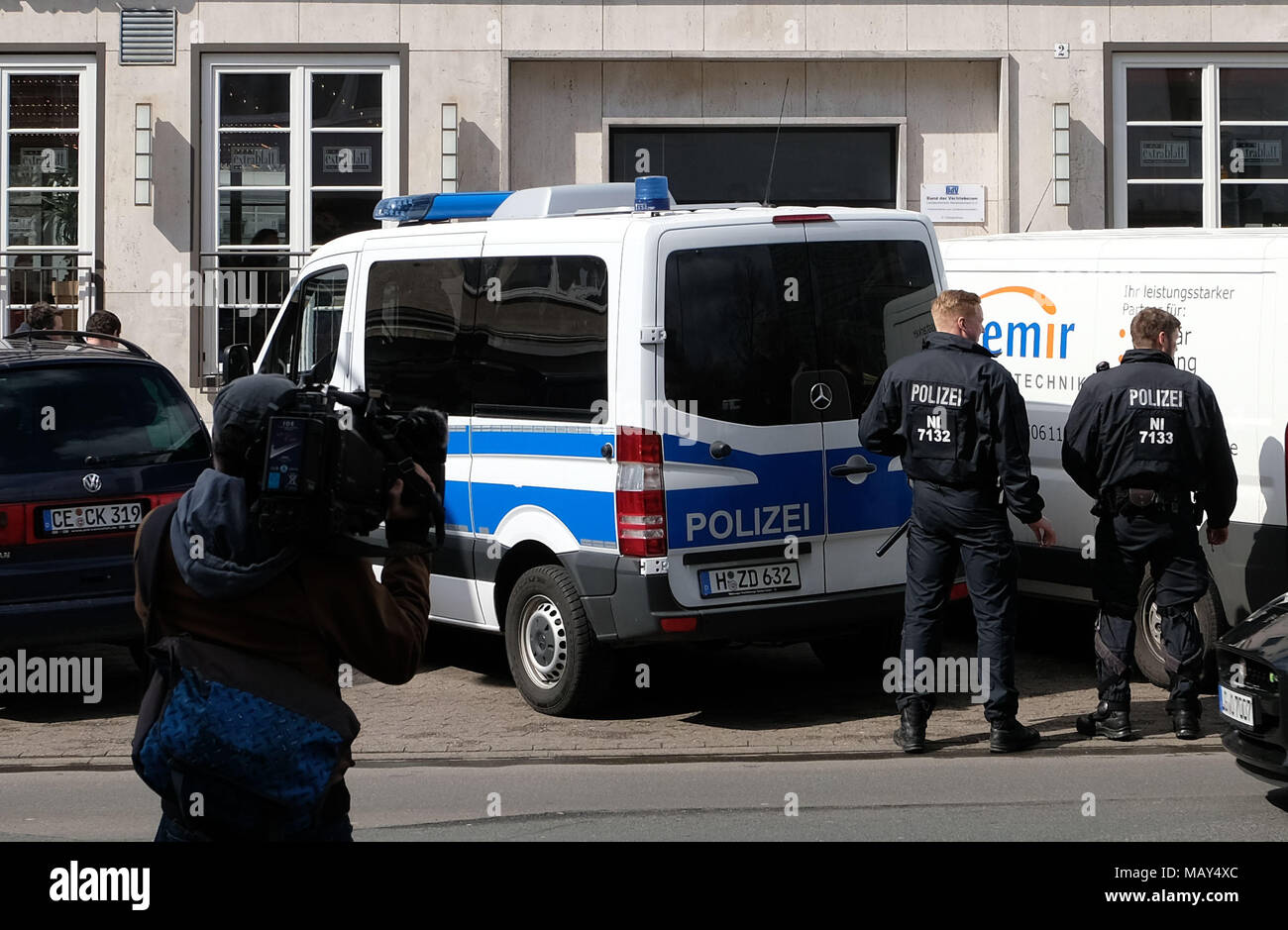 Hannover, Germany. 05 April 2018, Germany, Hannover: Two police officers standing during a raid in front of the building of the Kurdish democratic social centre in Hannover. The association is, according to itself, the umbrella organisation of the Kurdish People's Council. Photo: Peter Steffen/dpa Credit: dpa picture alliance/Alamy Live News - Stock Image