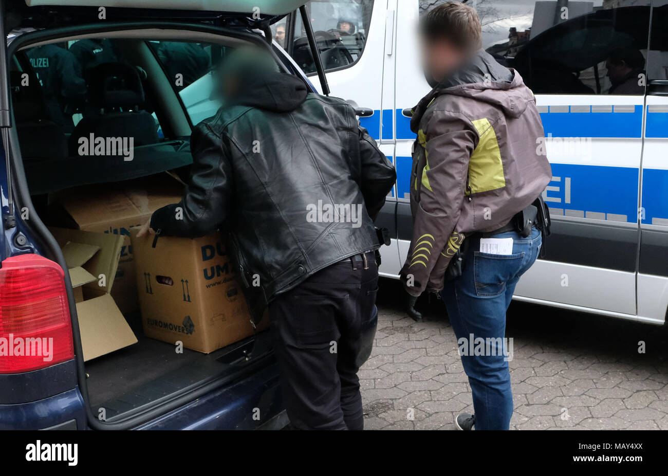 Hannover, Germany. 05 April 2018, Germany, Hannover: Two police officers in civil clothing carrying boxes of confiscated documents to a car during a raid of the Kurdish democratic social centre in Hannover. The association is, according to itself, the umbrella organisation of the Kurdish People's Council. Photo: Peter Steffen/dpa - ACHTUNG: Die Personen wurden auf Anforderung der Polizei zum Schutz der Identität der Beamten gepixelt. Credit: dpa picture alliance/Alamy Live News - Stock Image