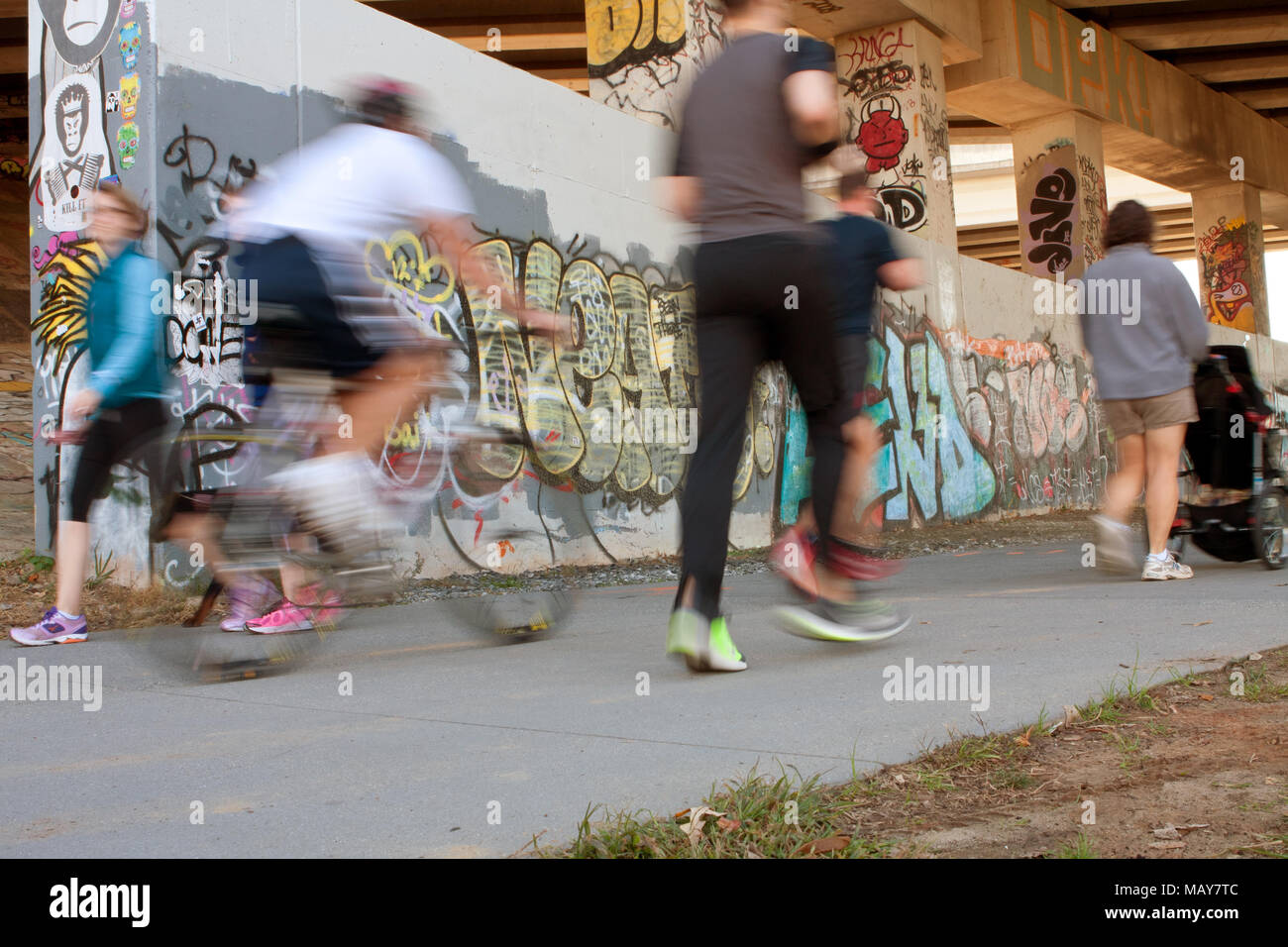 Motion blur of several people exercising along a graffiti covered trail that is part of the Atlanta Beltline, on November 2, 2013 in Atlanta, GA. - Stock Image