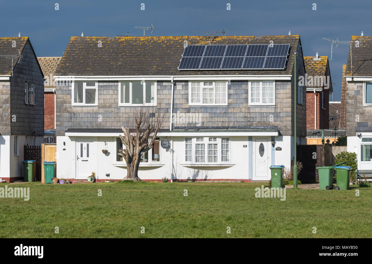 Modern Tile Hung house with solar panels next to a park in England, UK. - Stock Image