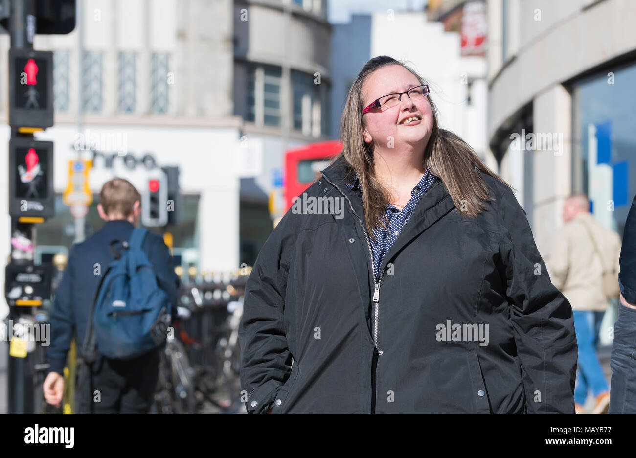 Young white female tourist visiting a new city and looking around at the sights. Woman sightseeing in a new place in the UK. - Stock Image