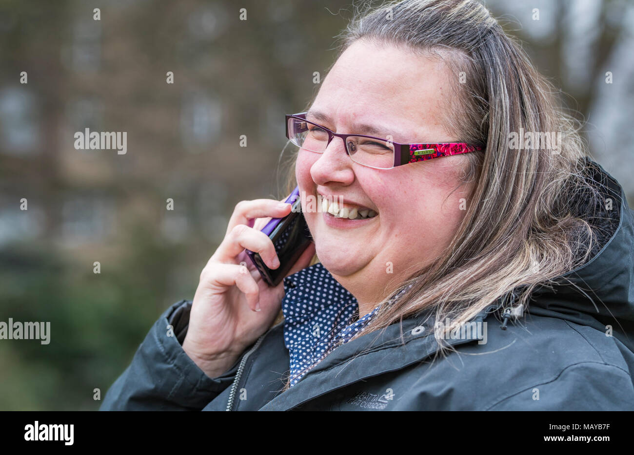 Young woman smiling and looking happy while speaking on a mobile phone. Happiness concept. Pleasing news. Happy news. - Stock Image