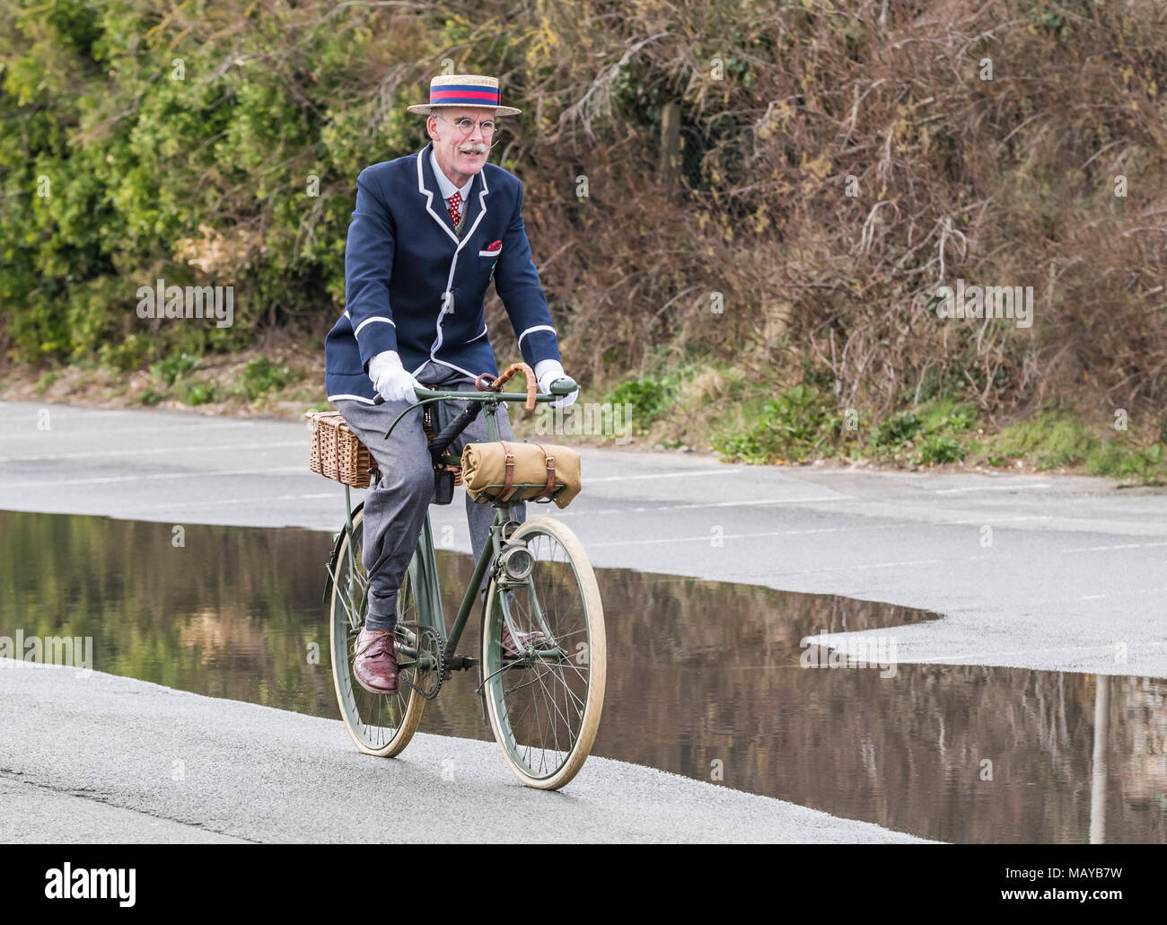 Elderly man cycling on a Victorian bicycle dressed in period costume wearing a blazer and straw boater hat, in the UK. Cyclist riding vintage bike. - Stock Image