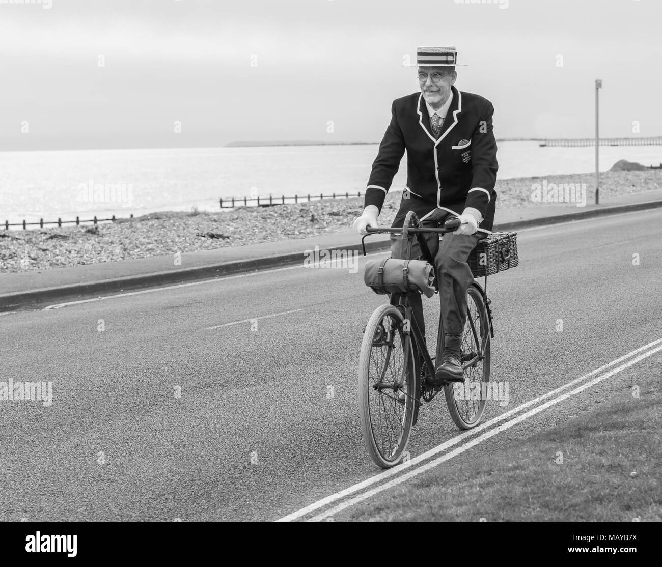 Senior man riding a Victorian bicycle dressed in period clothing and straw boater hat, in the UK, in black and white. Old cyclist riding vintage bike. - Stock Image