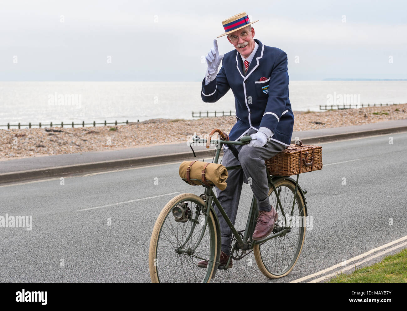 Elderly man cycling on a Victorian bicycle dressed in period costume wearing a blazer and straw boater hat, in the UK. Gentleman tipping hat. - Stock Image
