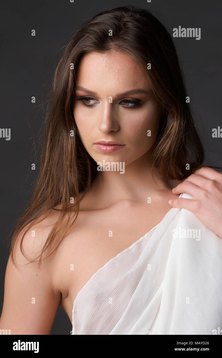 Headshot of a brunette girl with brown eyes looking away.  She is holding a white drape to cover her top which is somewhat translucent - Stock Image