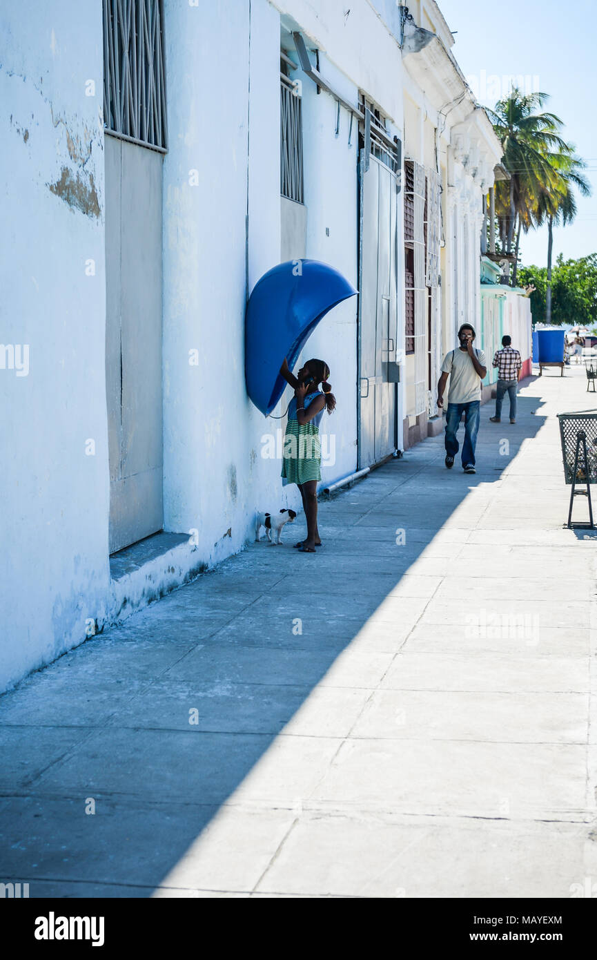 Girl making call from public payphone a little dog waits by her, Cienfuegos, Cuba - Stock Image