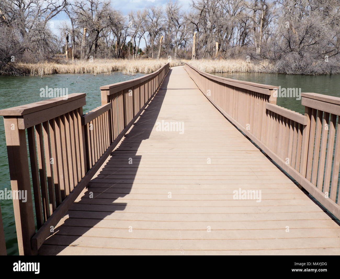 A long walkway, made of composite material, spans over water. - Stock Image