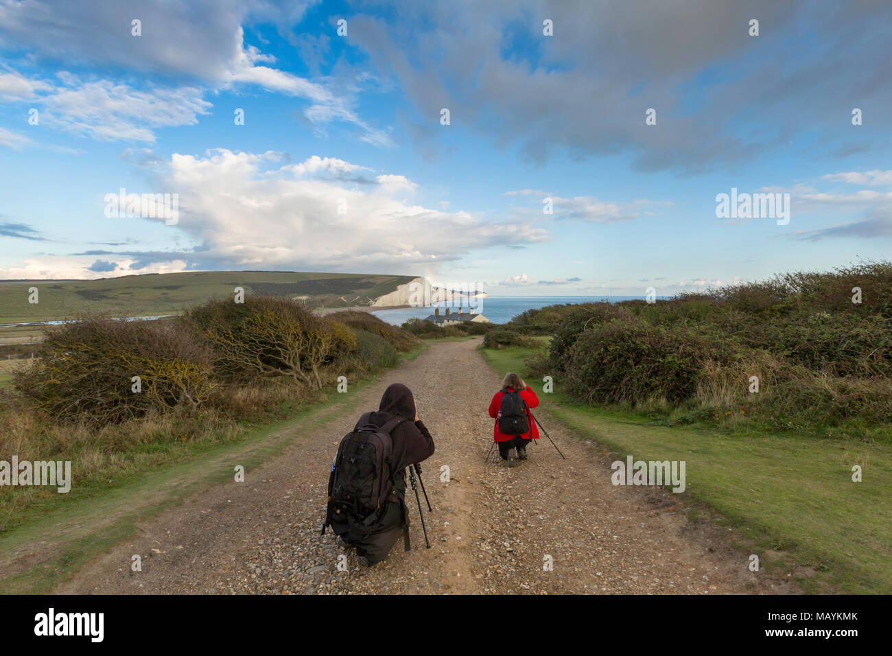 Two photographers with tripods at Seaford photographing the classic view of the Seven Sisters chalk cliffs on the South Downs Way, East Sussex, UK. Stock Photo