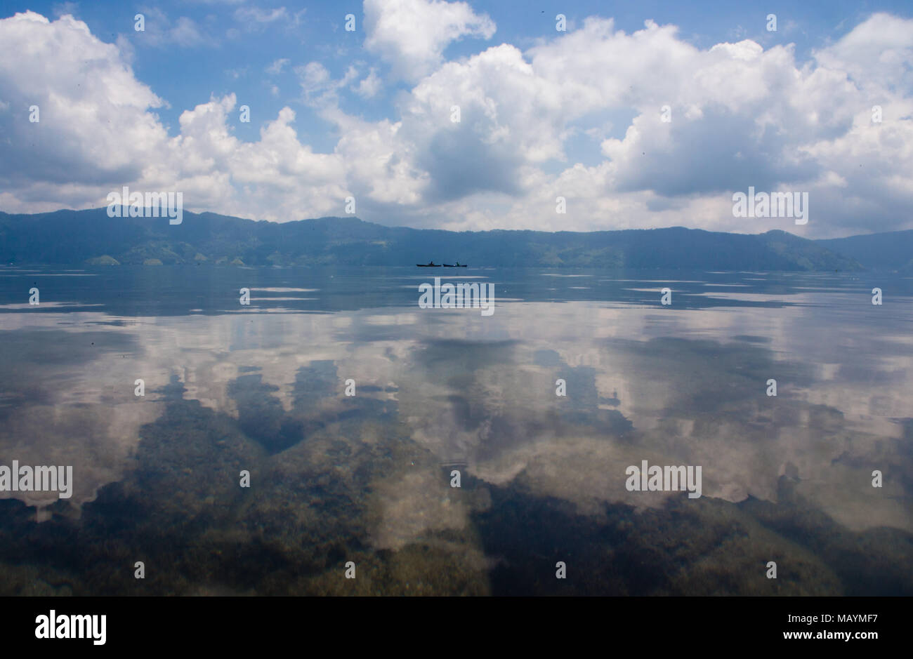 Lake Toba is one not the largest Volcanic lakes. You can see the rocks peaking through the clear fresh water. - Stock Image
