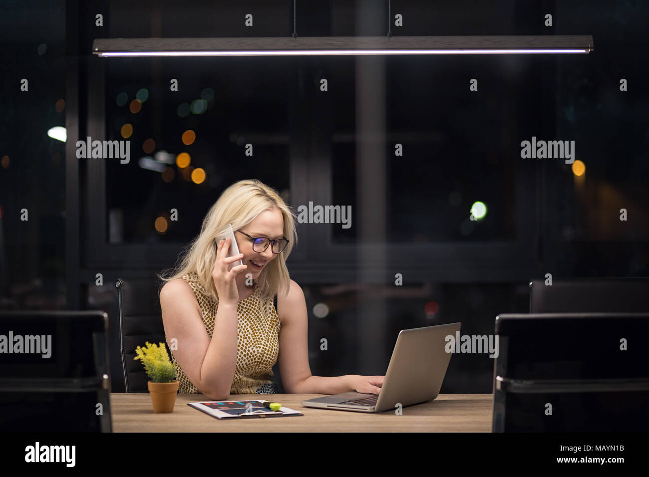 Young beautiful caucasian woman working on laptop in the modern office overtime - Stock Image