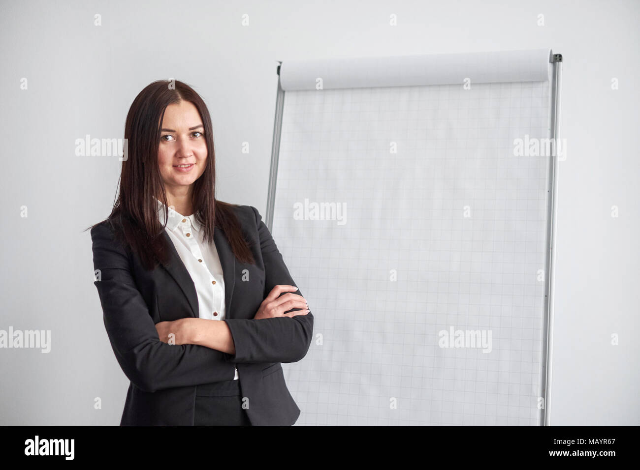 Portrait of young smiling businesswoman standing nearflipchart in office. - Stock Image