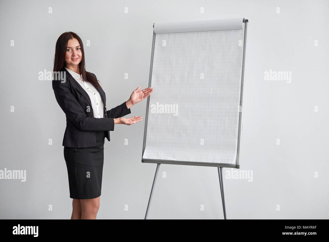 Portrait of young smiling businesswoman standing nearflipchart in office and pointing on it. - Stock Image