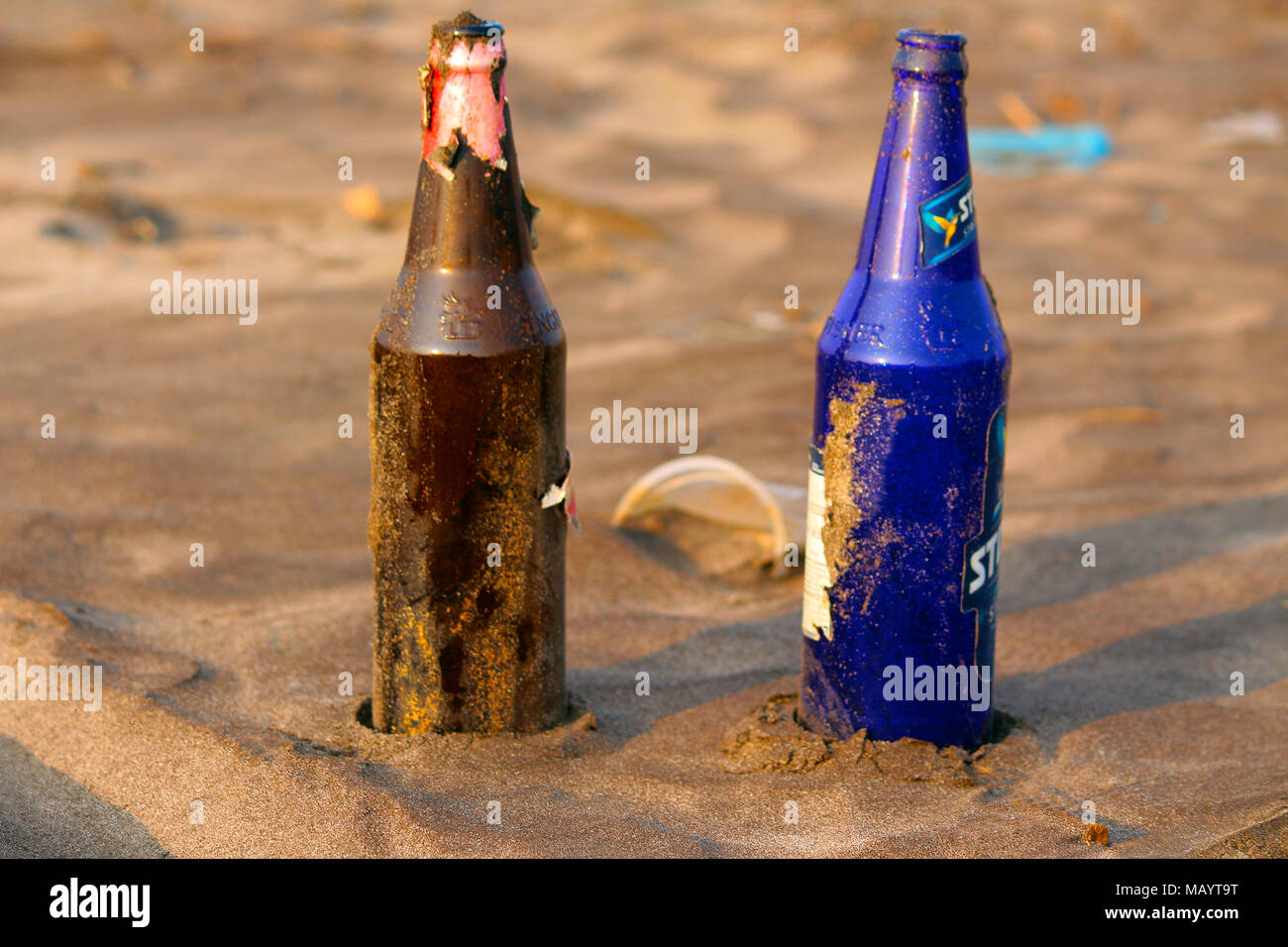 Two different color glass bottles on beach at Palande, Kokan Stock Photo