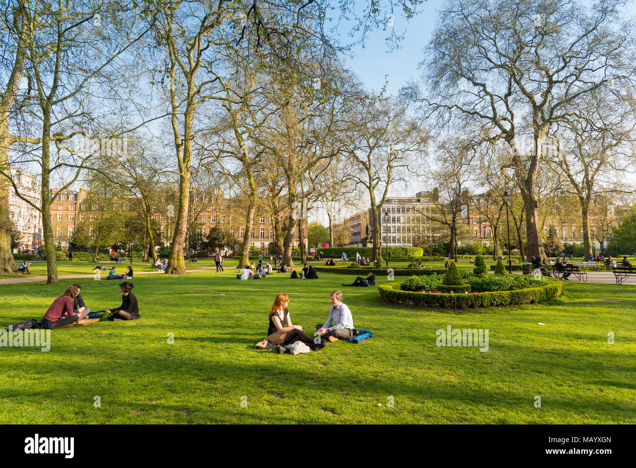 People sitting on the grass in Russell Square, Bloomsbury, London, UK - Stock Image