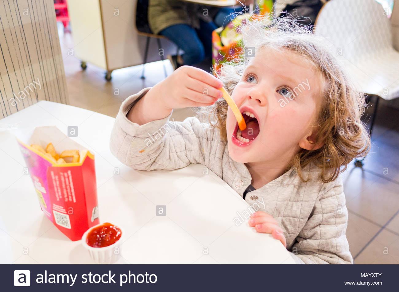 Toddler eating McDonald's french fries, UK - Stock Image