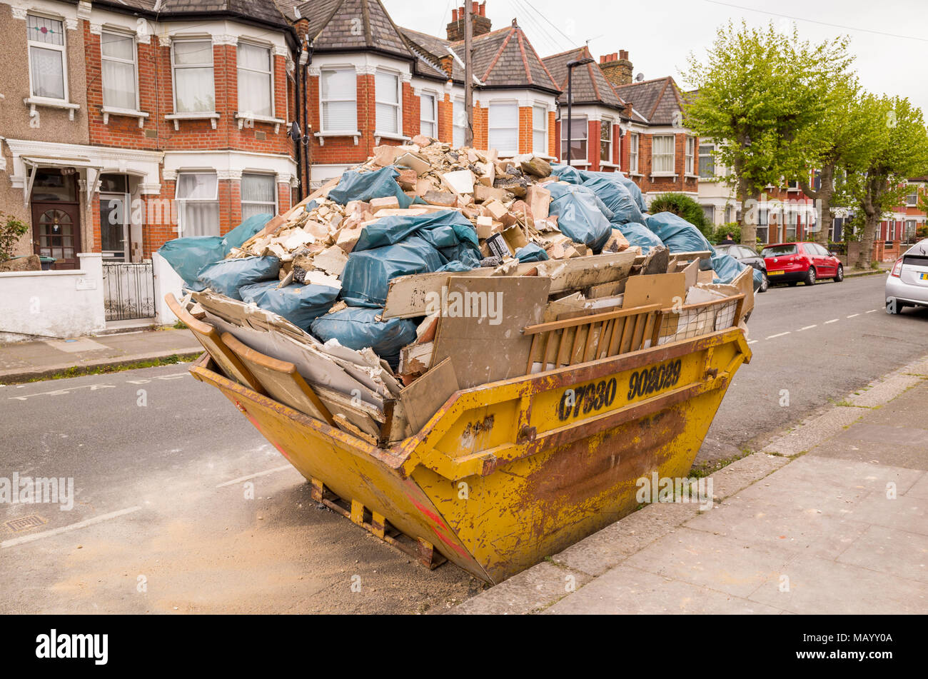 Builder's rubble in full skip on a terraced street, Haringey, North London, UK - Stock Image